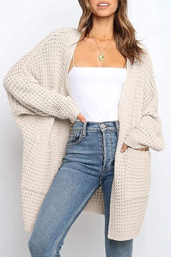 model wearing oversized cardigan with big sleeves and pockets paired with a tank top