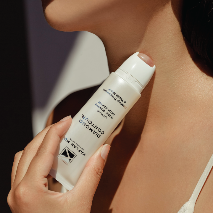 A model rolling the neck serum onto their neck