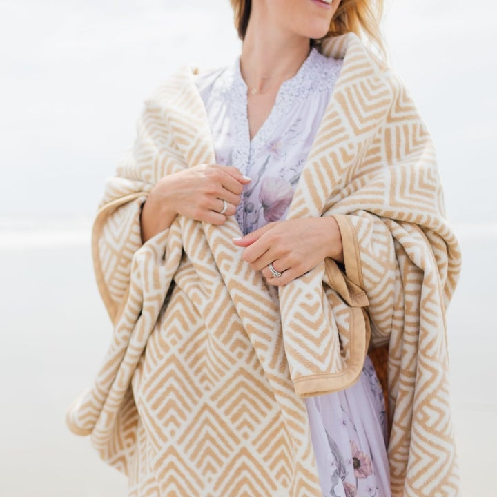 model wrapped in tan and cream patterned blanket