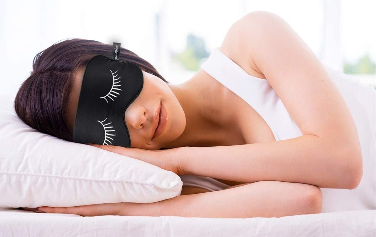 A person sleeps with an eye mask that has eyelashes on it