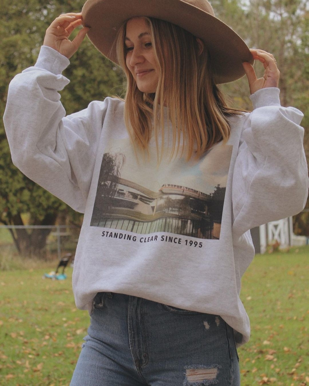 "a model wearing an oversized gray heathered sweatshirt with a vintage photo of the monorail on it and the words ""standing clear since 1995"""