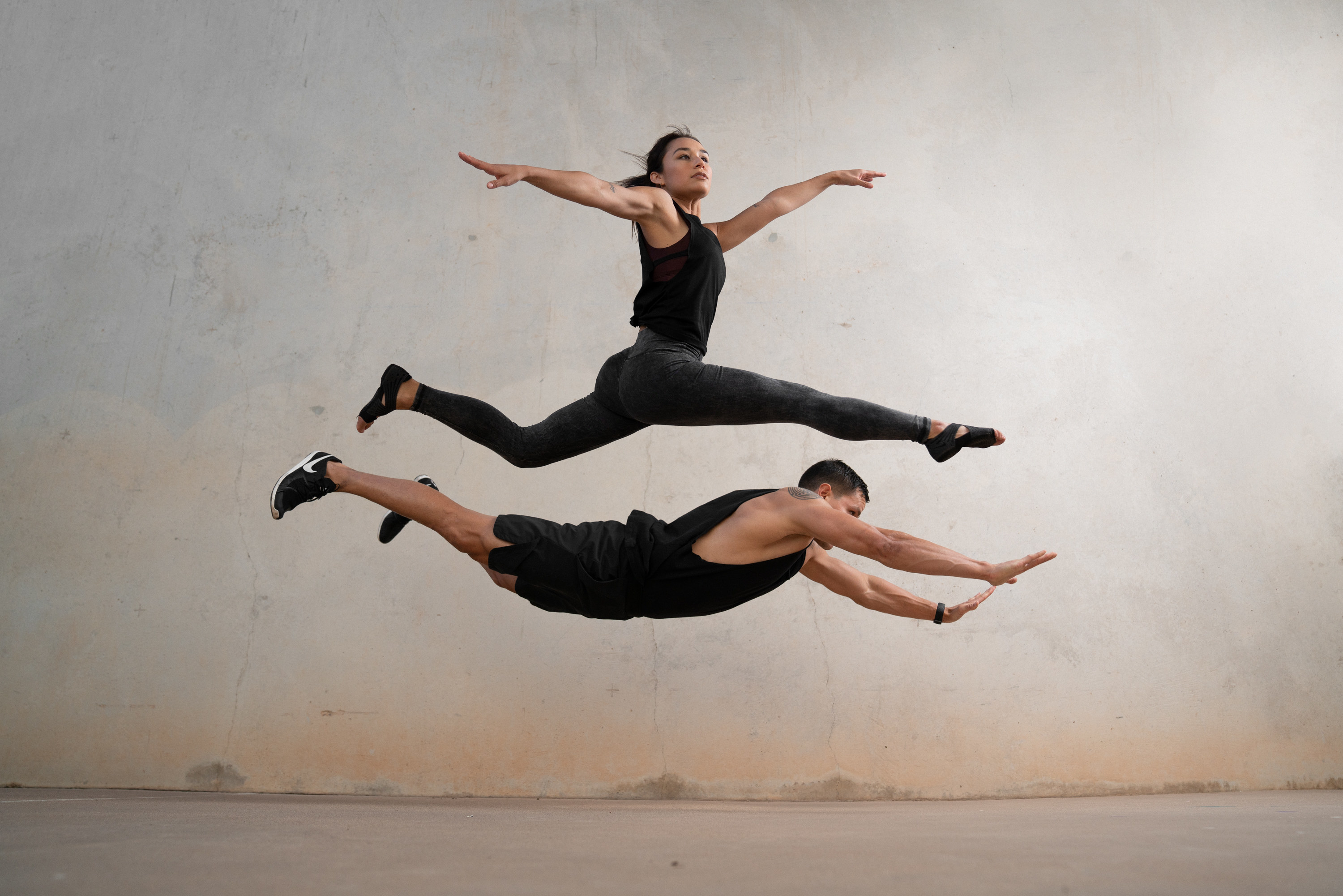 A woman in black and a man in black shorts and tank top leaping, the woman over the man.