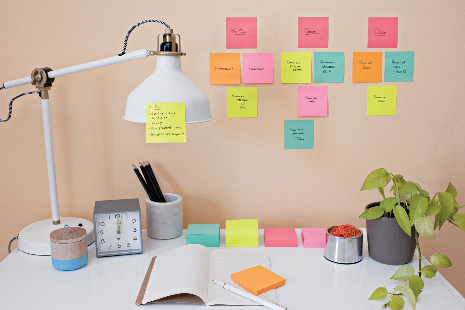 A wall with different bright-colored sticky notes on it