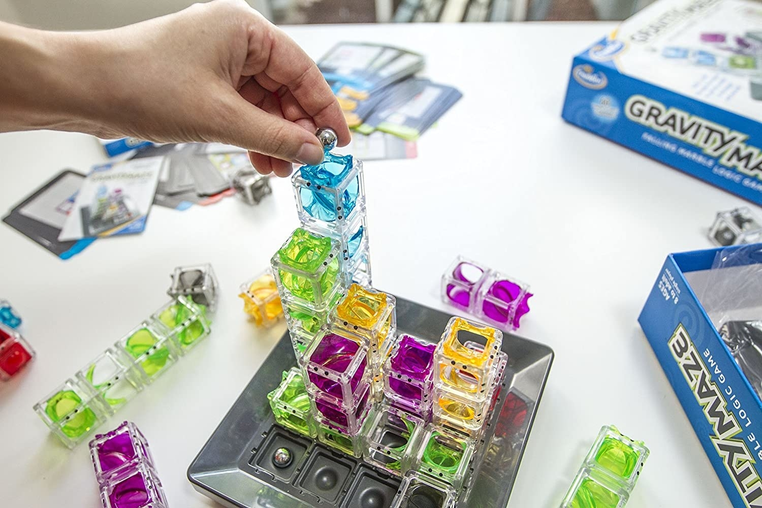 a model placing a marble into the top of clear stacked cubes on the board of the game