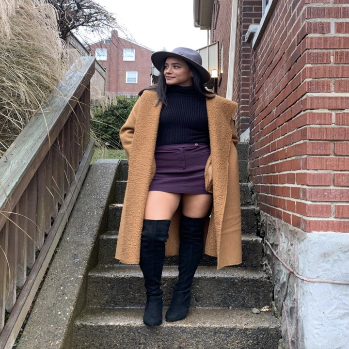 reviewer wearing the black boots with mini skirt