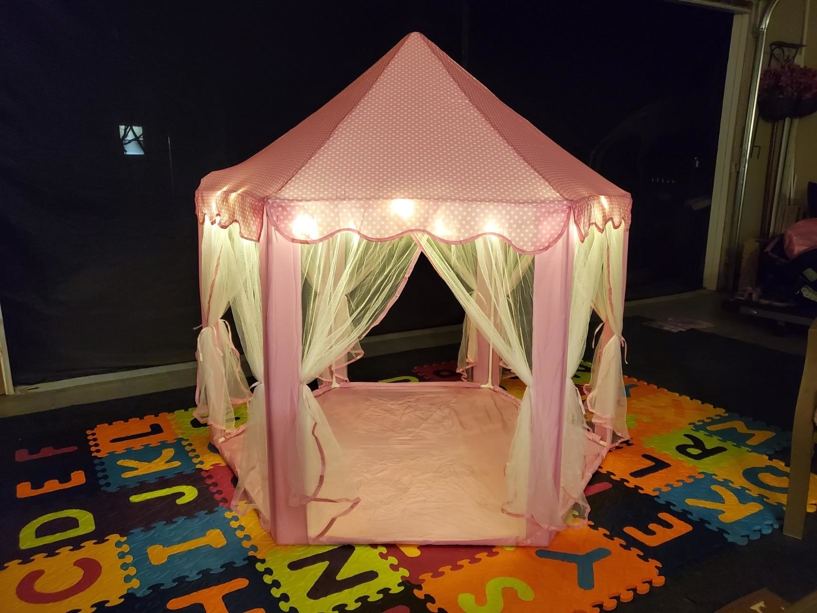 a pink princess castle with tulle drapes and string lights throughout