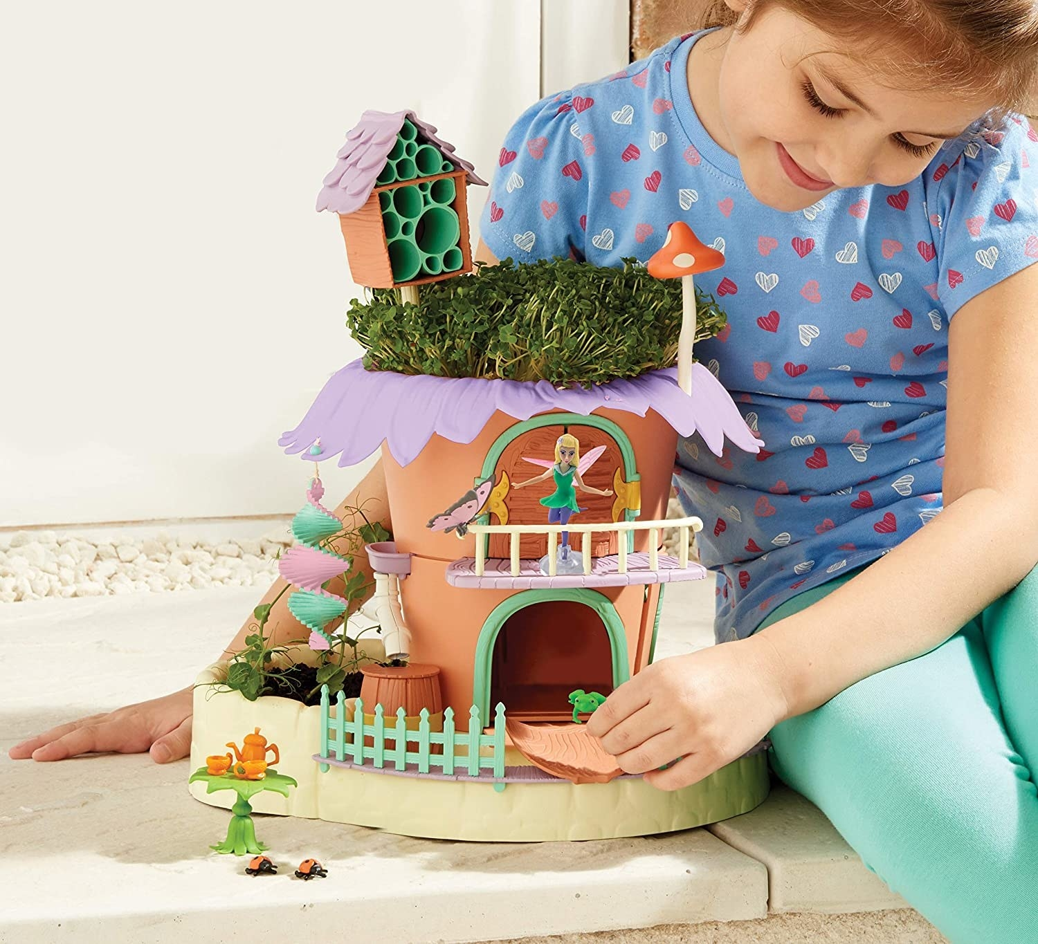 a child model playing with the fairy garden cottage