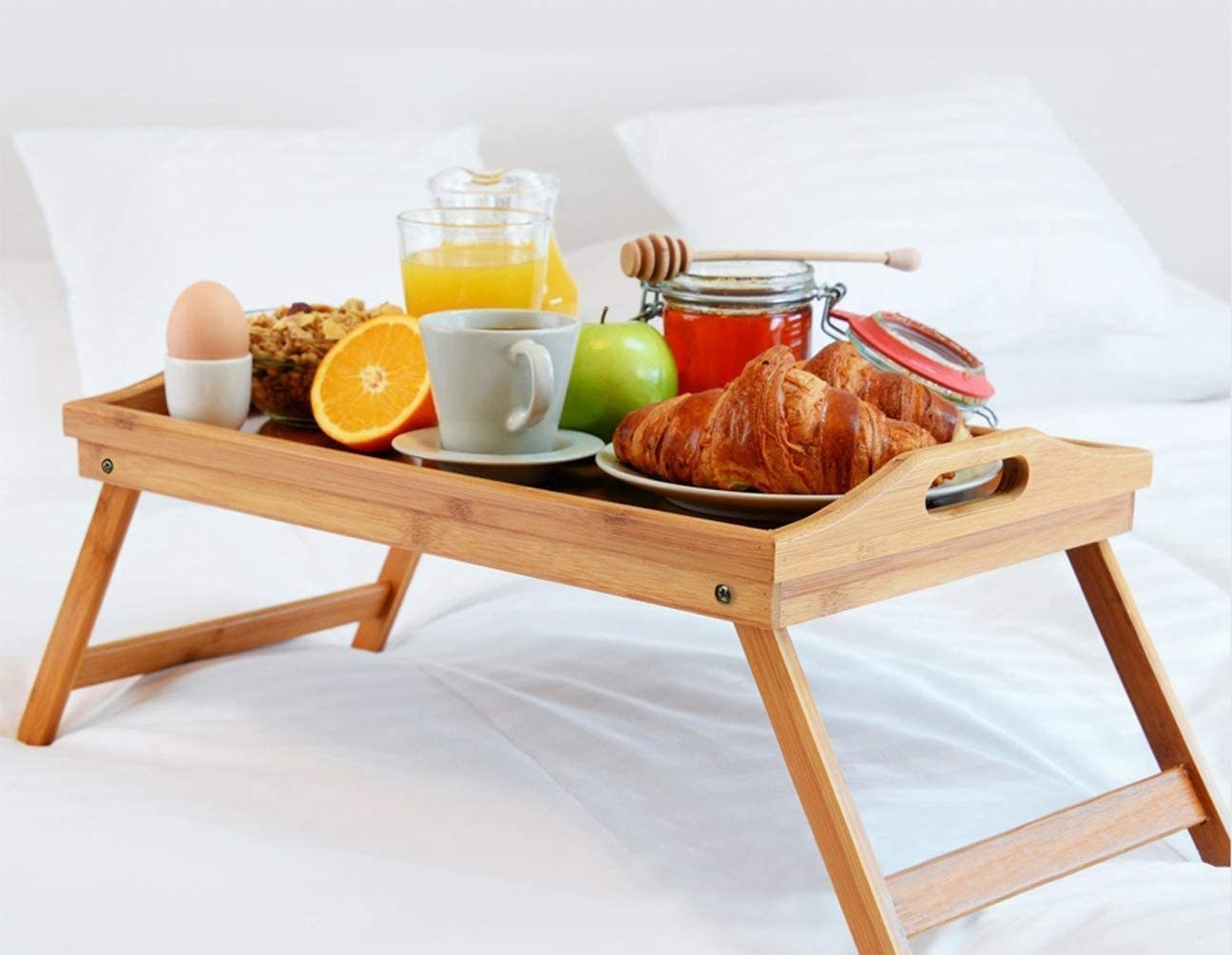 A tray on a bed with breakfast foods