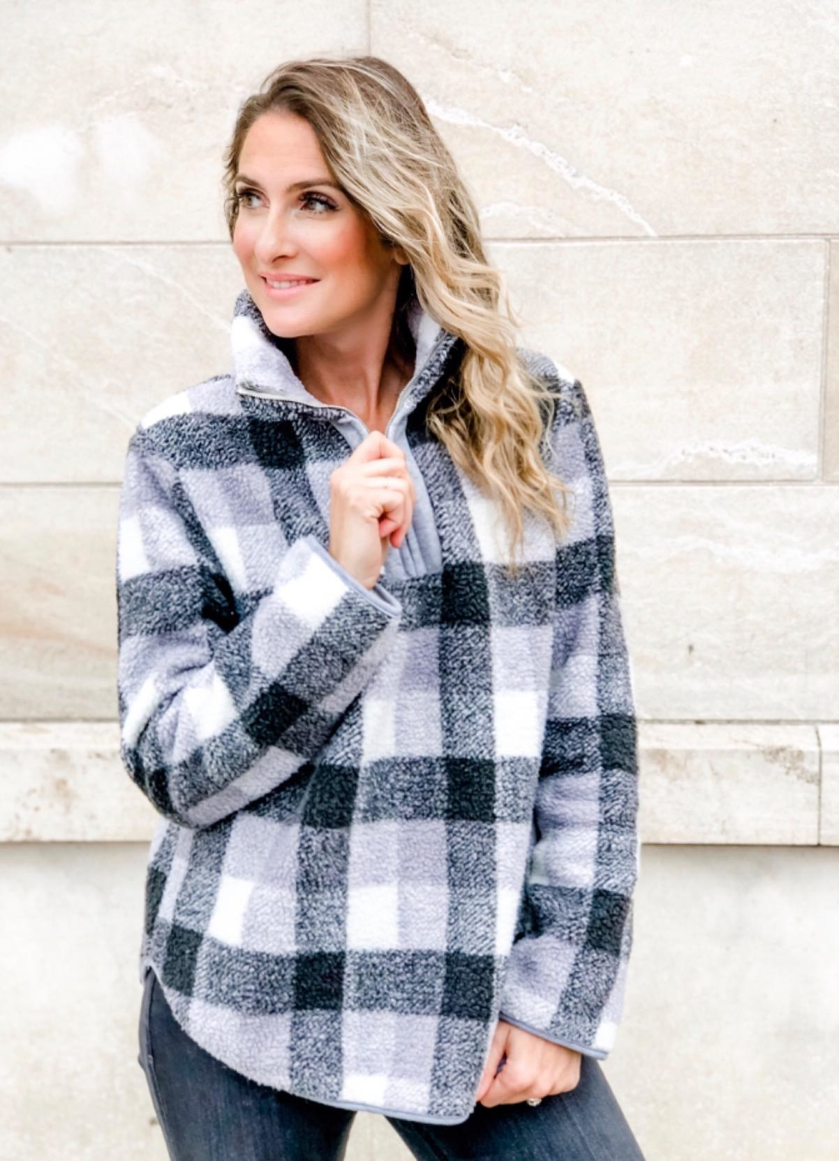 Reviewer wearing the fuzzy quarter zip in black, grey, and white plaid print