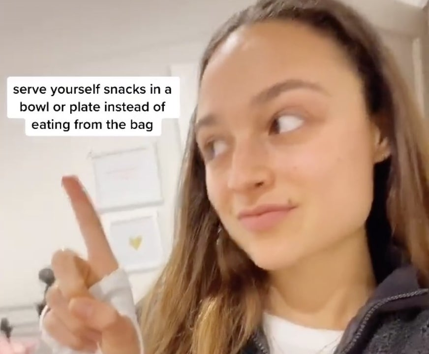 """A woman pointing to on screen text that says """"serve yourself snacks in a bowl instead of eating from the bag"""""""
