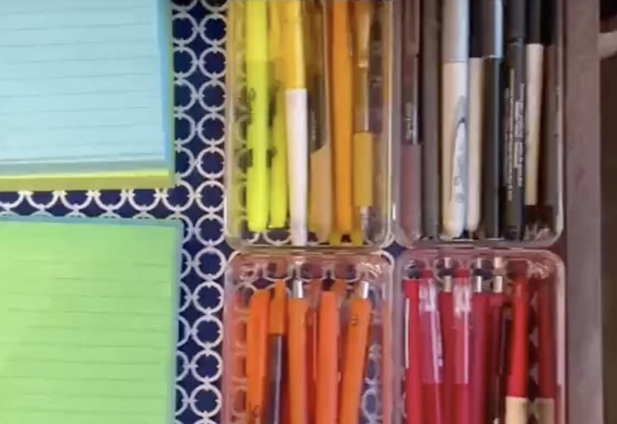 An organized drawer with colorful pens