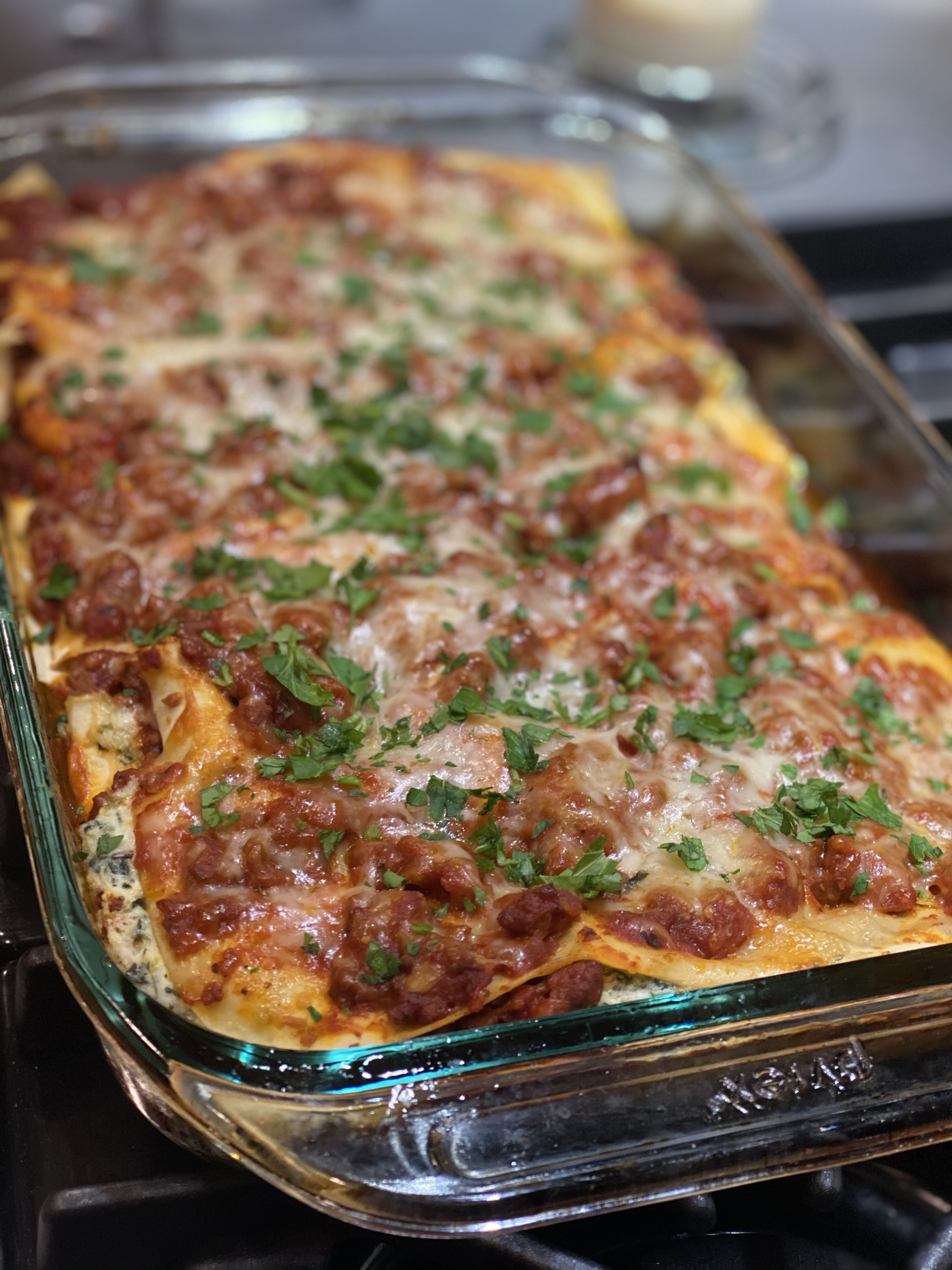 A baking dish filled with lasagna topped with tomato and meat sauce.