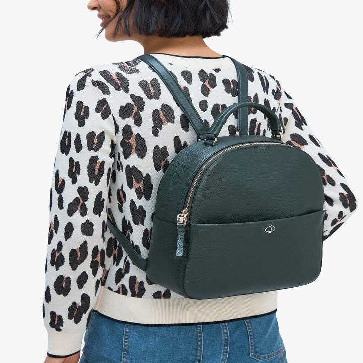 Model wearing a dark green backpack purse