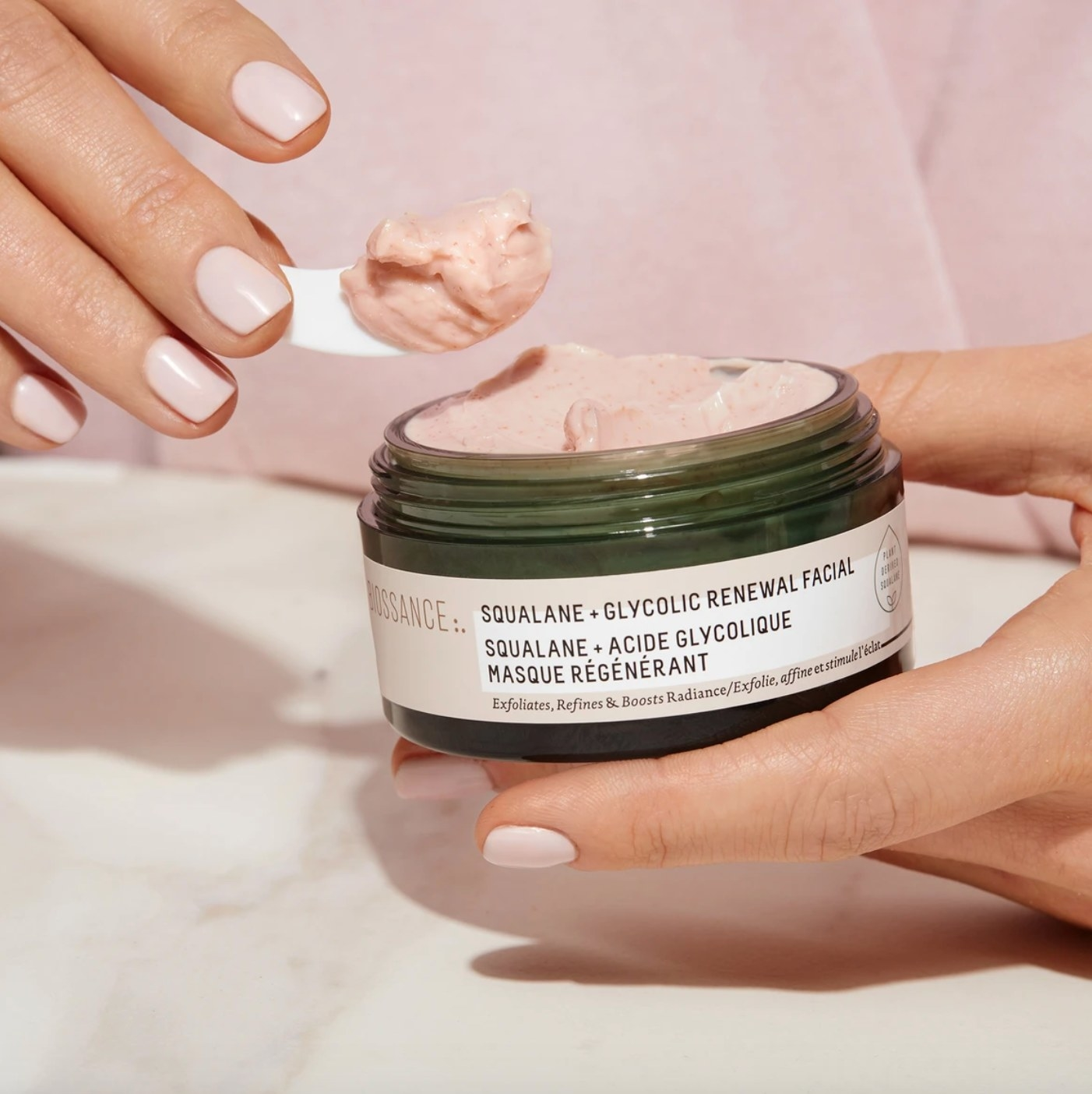 The squalane and glycolic renewal facial being scooped out of it's green jar