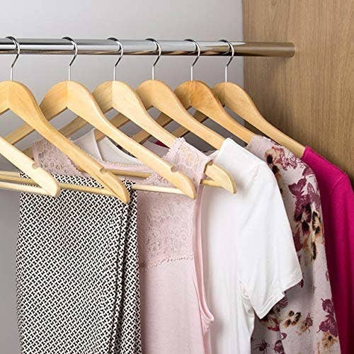 Clothes hung up on the wooden hangers.