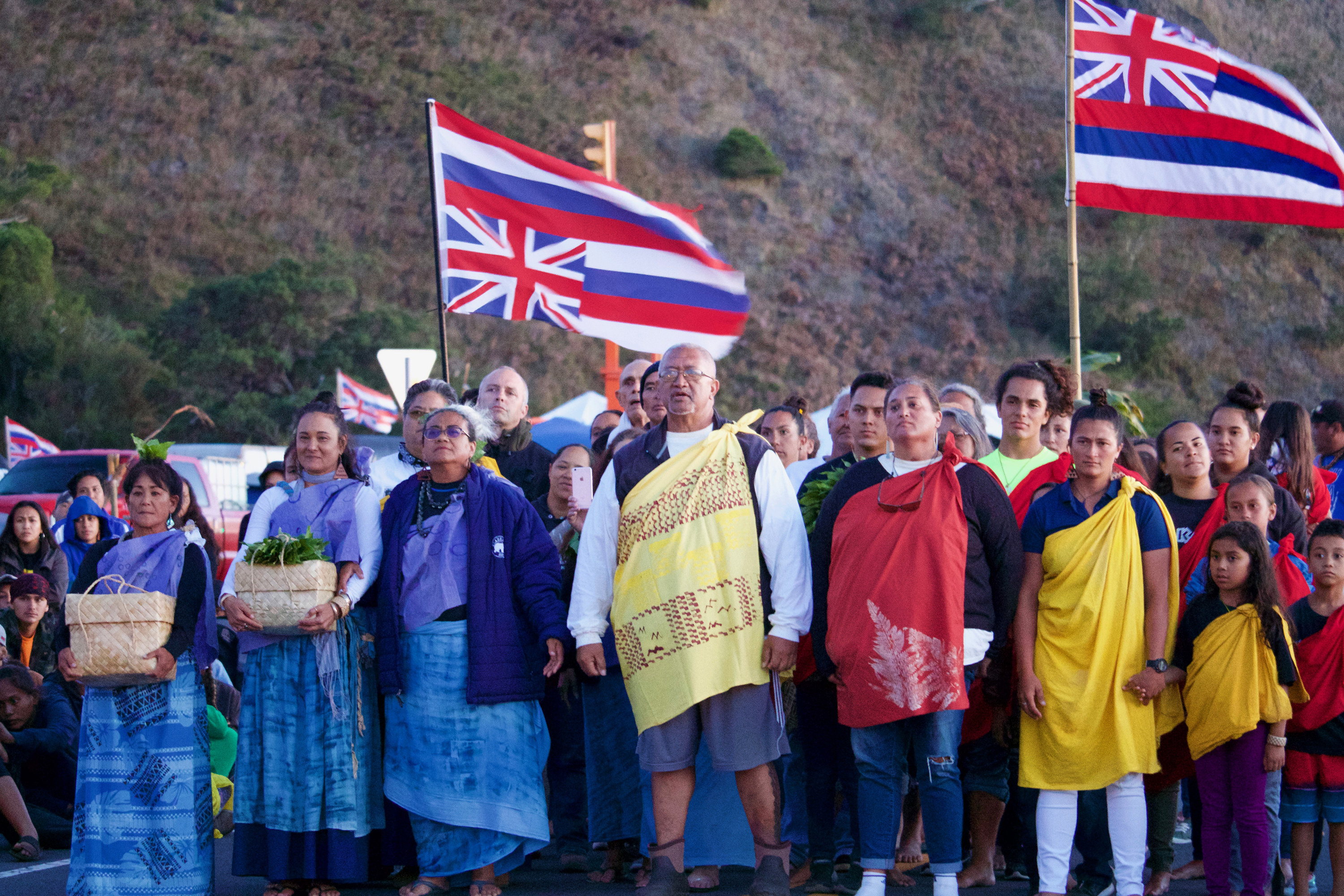 A group of Hawaii'ians with two flags in front of a natural background.