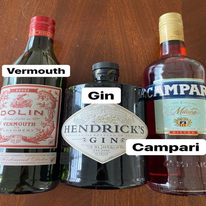 Bottles of vermouth, gin, and Camprari for a Negroni.