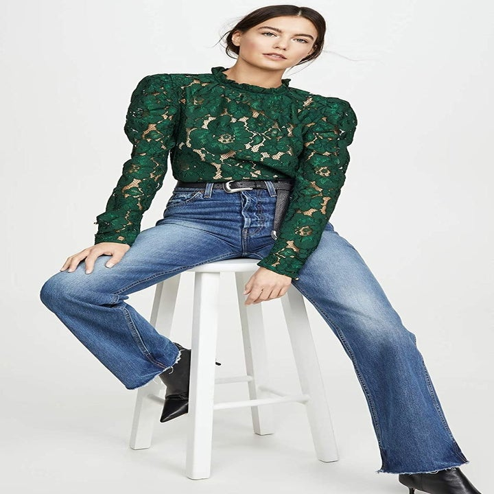 A model wearing the long-sleeve, high-neck top in green