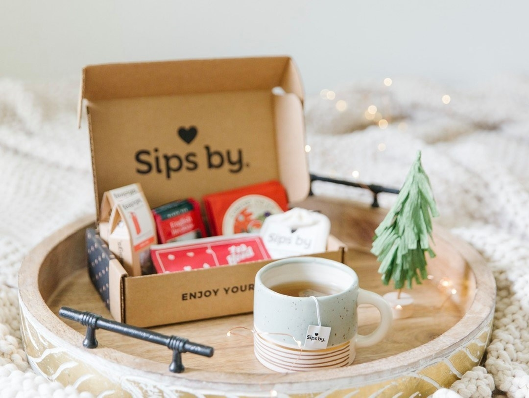 A Sips by box on a tray with a Christmas vibe and a hot cup of tea next to it