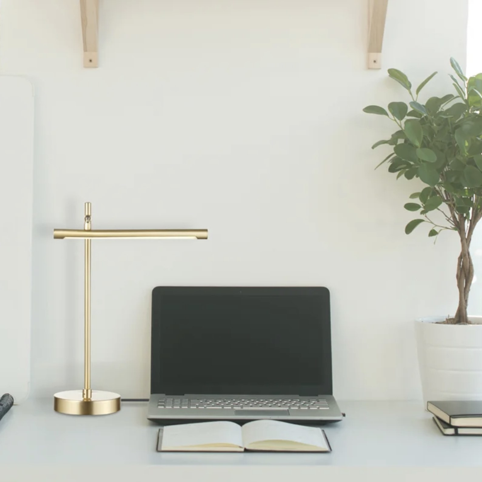 The brass desk lamp next to a laptop