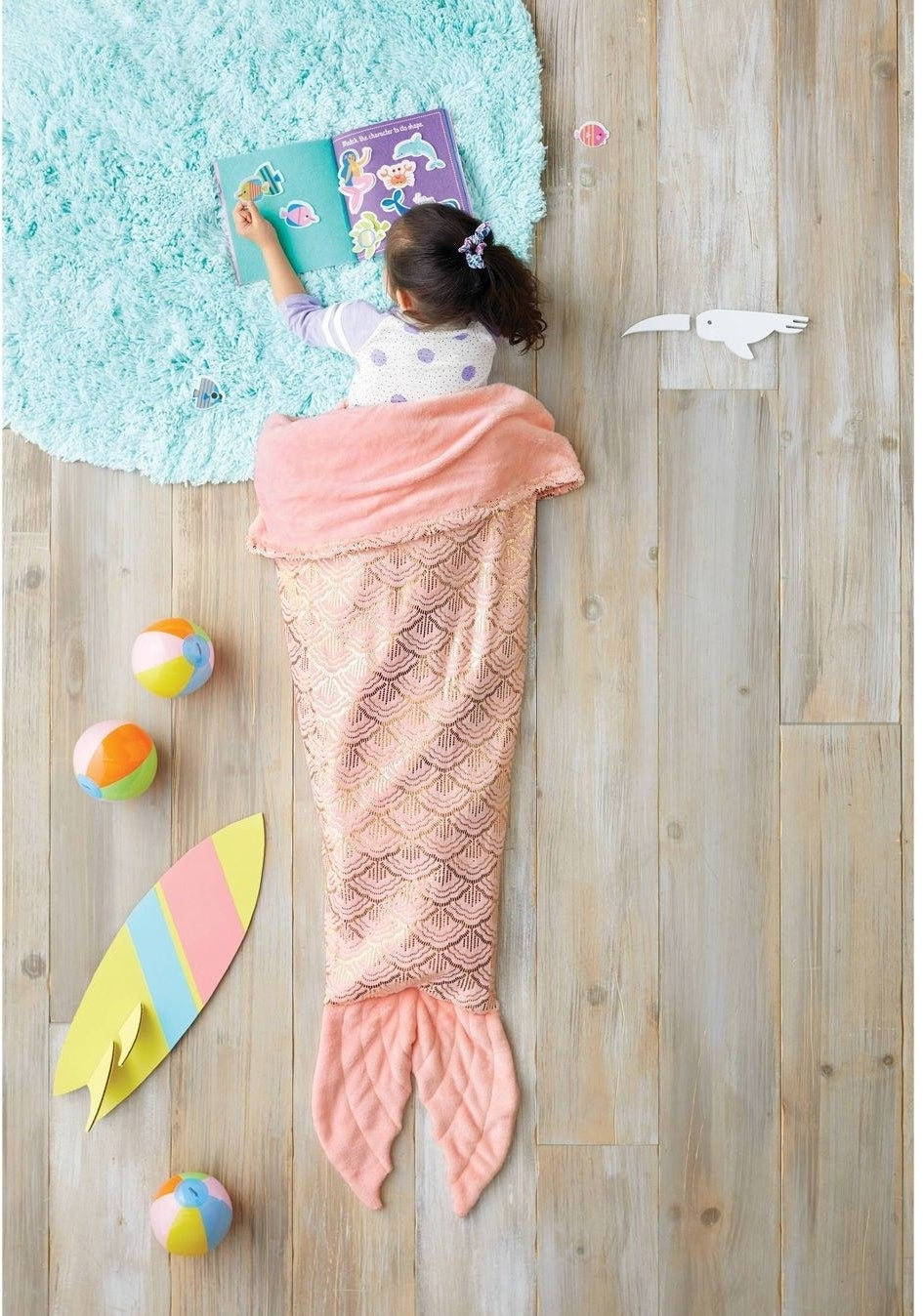 A child wrapped in a sparkly pink blanket that makes them look like they have a mermaid tail