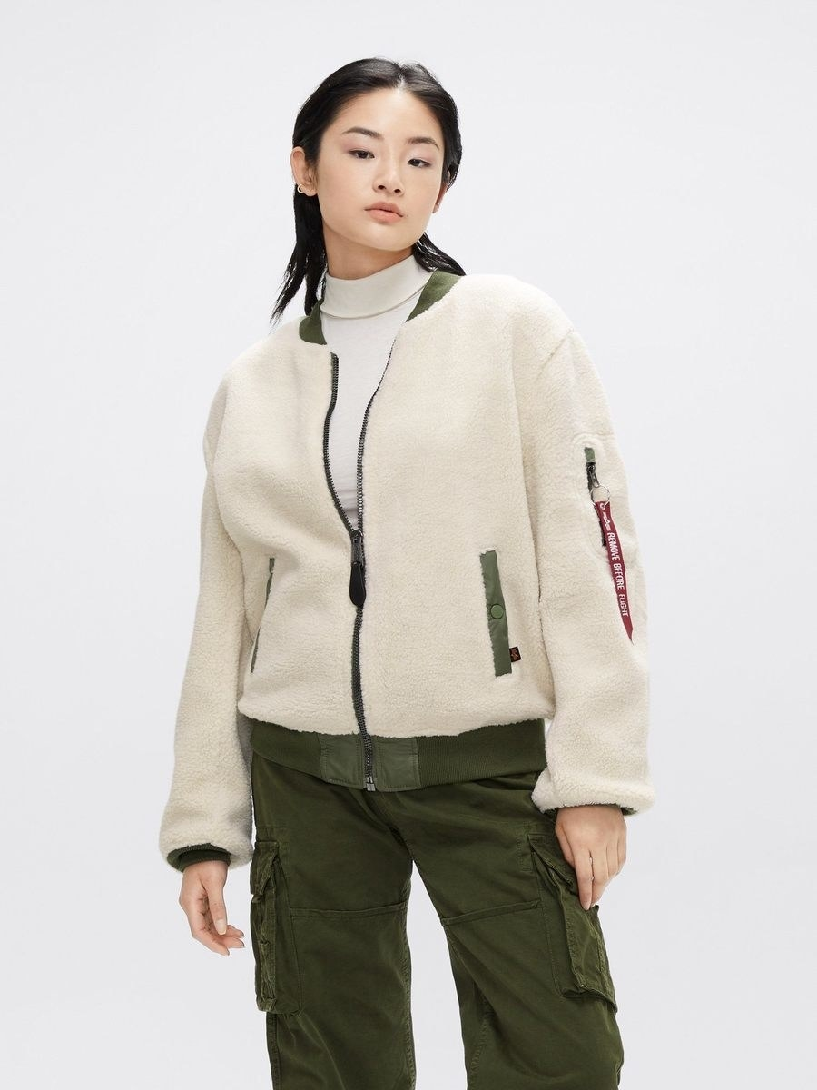 a model wears the l-2b sherpa bomber in light cream