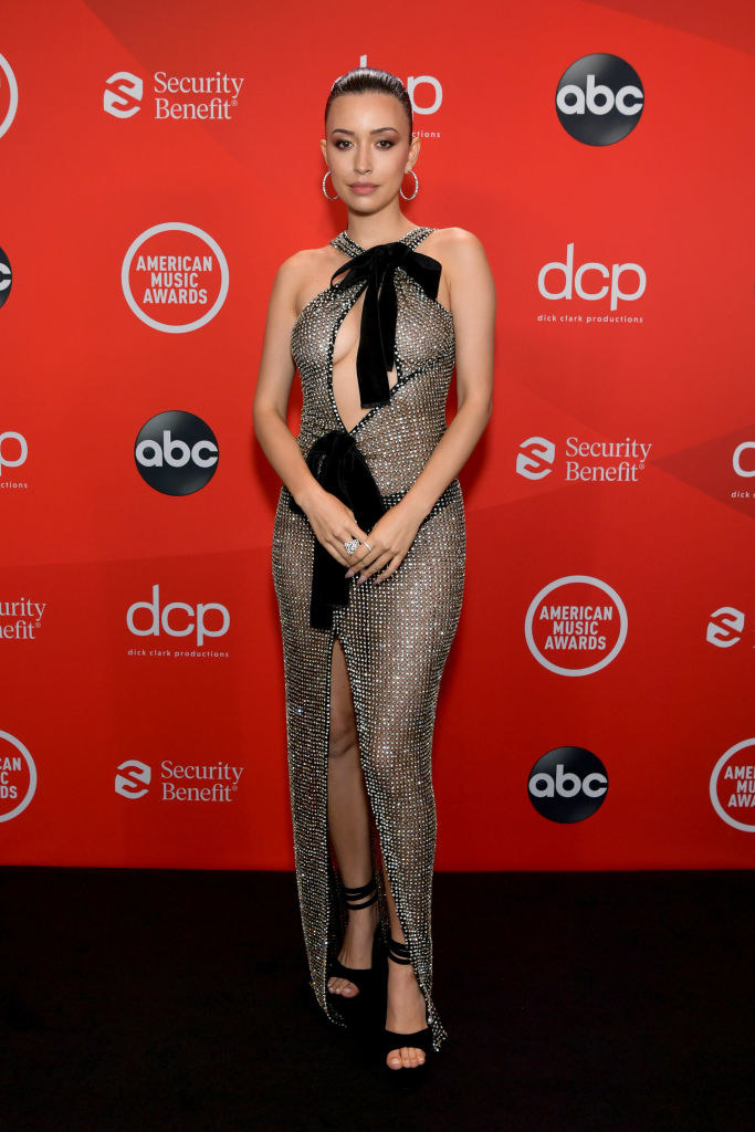 Christian Serratos attends the 2020 American Music Awards in a mesh gown featuring a bow at the neckline