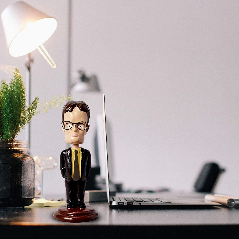 Dwight Shrute bobble head styled on a desk