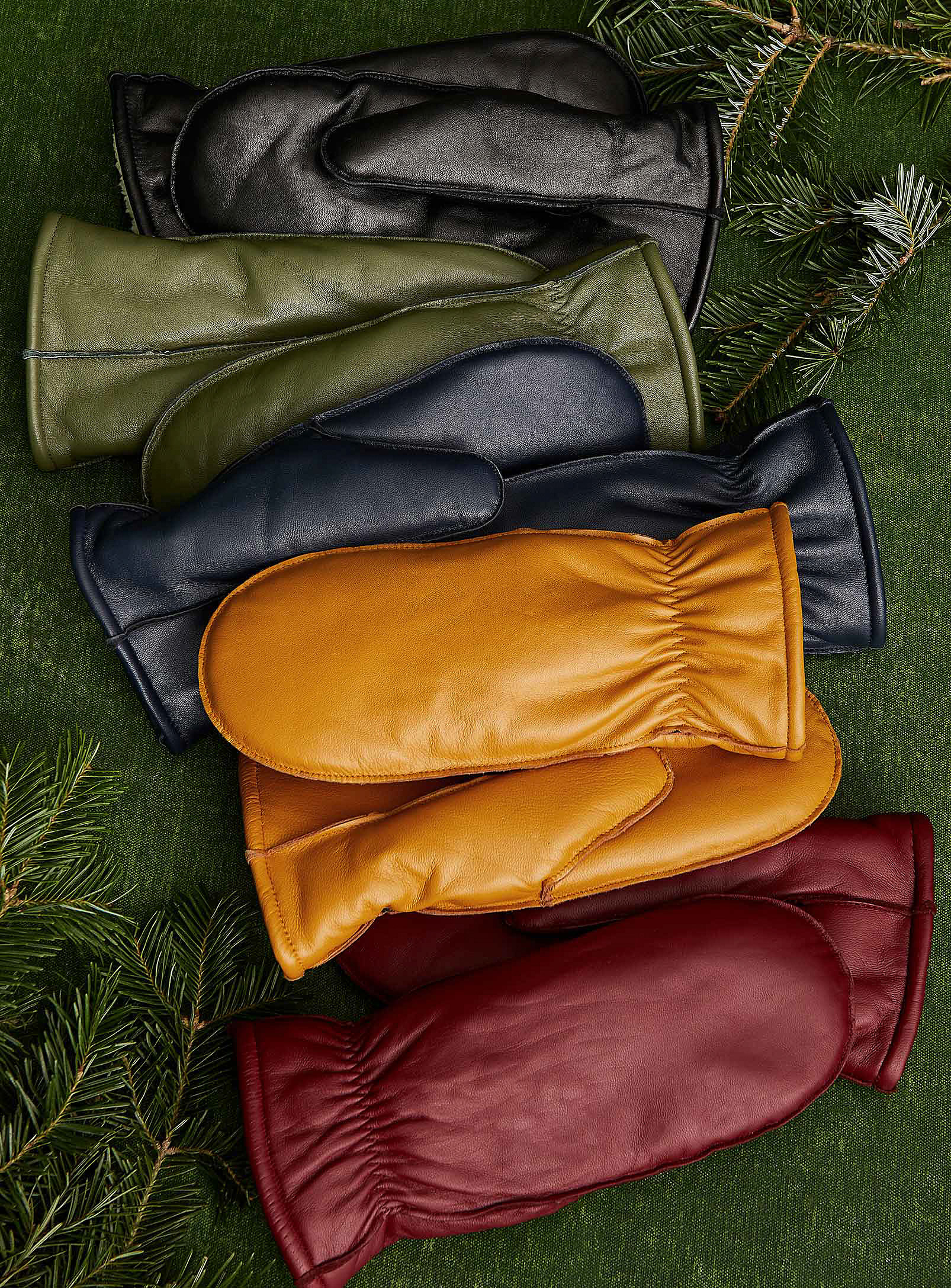 Five pairs of leather mittens on a plain background