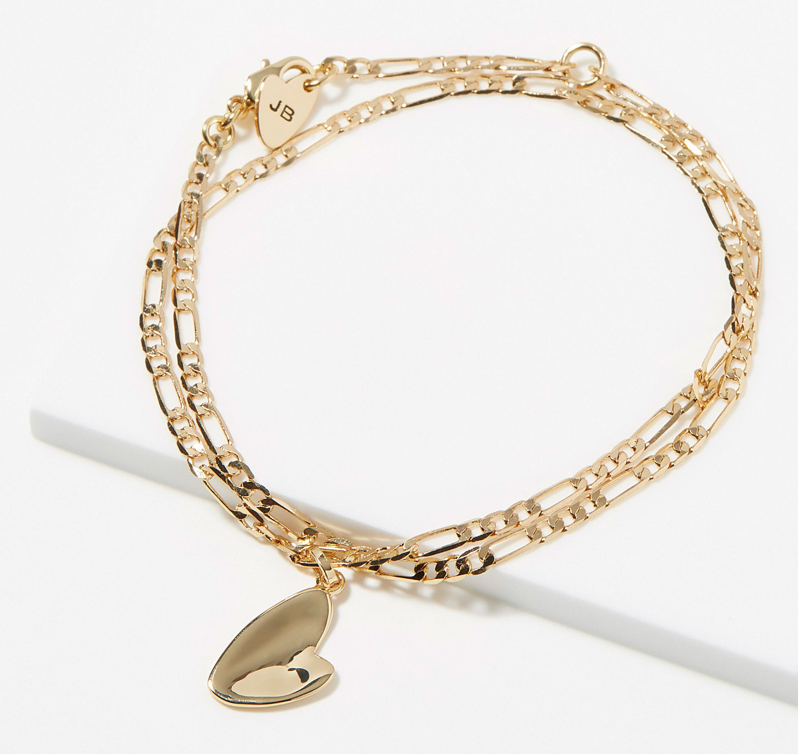 A gold chain bracelet with a heart pendant