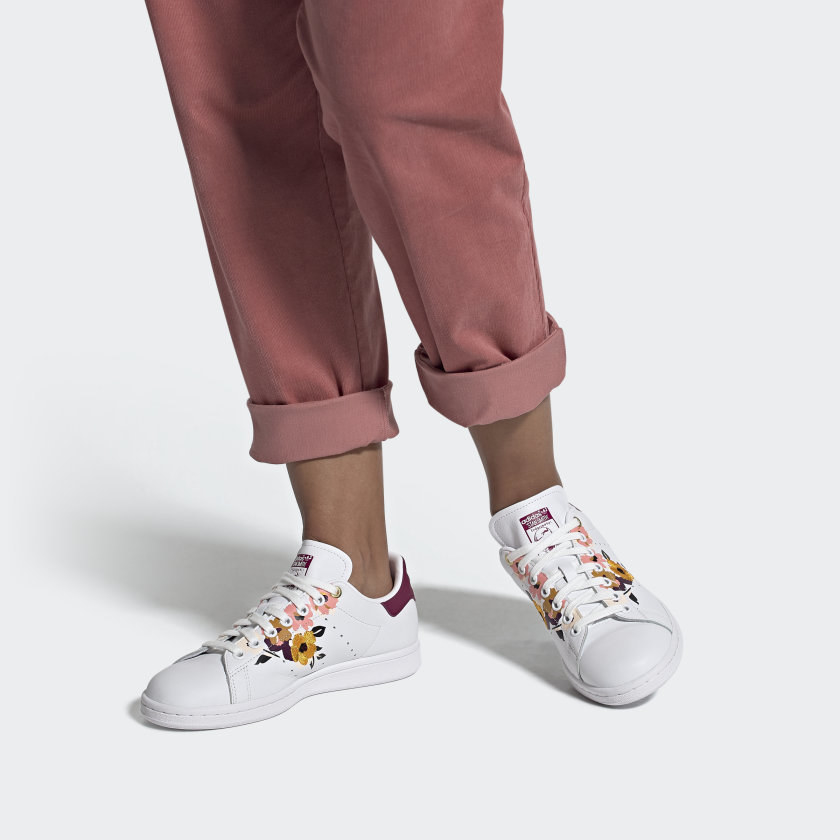 Model wearing white sneakers with pink and gold embroidered flowers