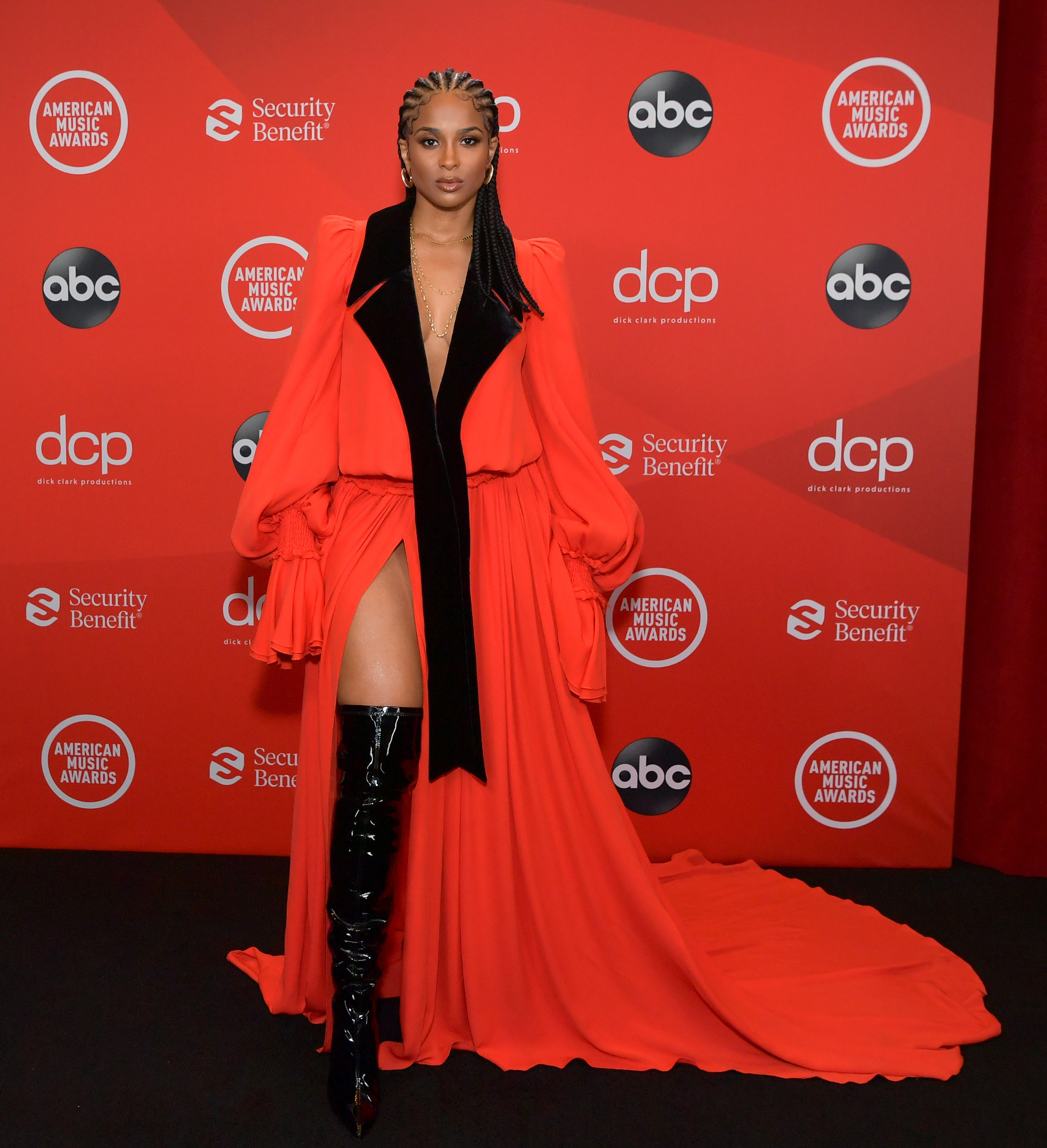 Ciara attends the 2020 American Music Awards wearing corn rows, a long gown, and thigh-high boots