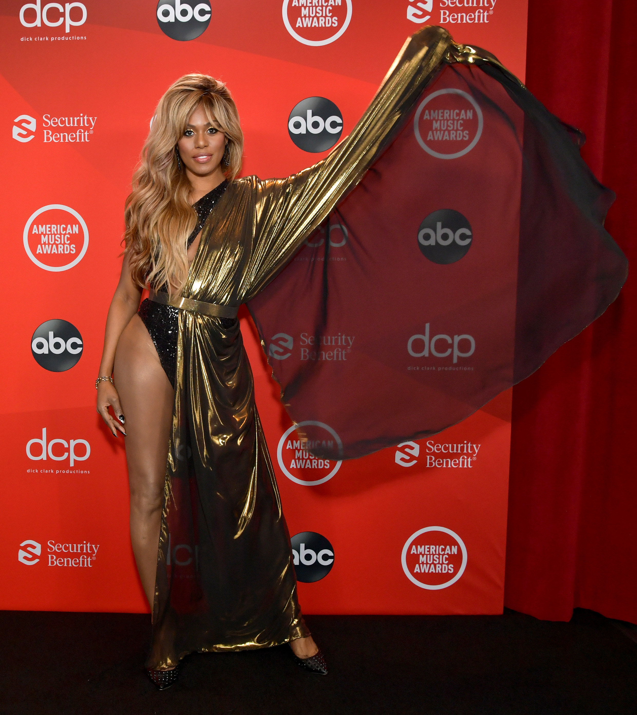 Laverne Cox attends the 2020 American Music Awards in a metallic bodysuit and gown