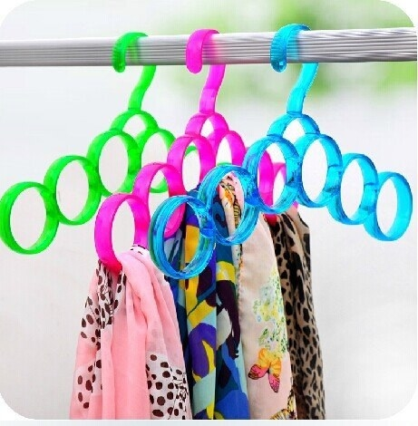 Scarves arranged on the circular loops of the hanger.