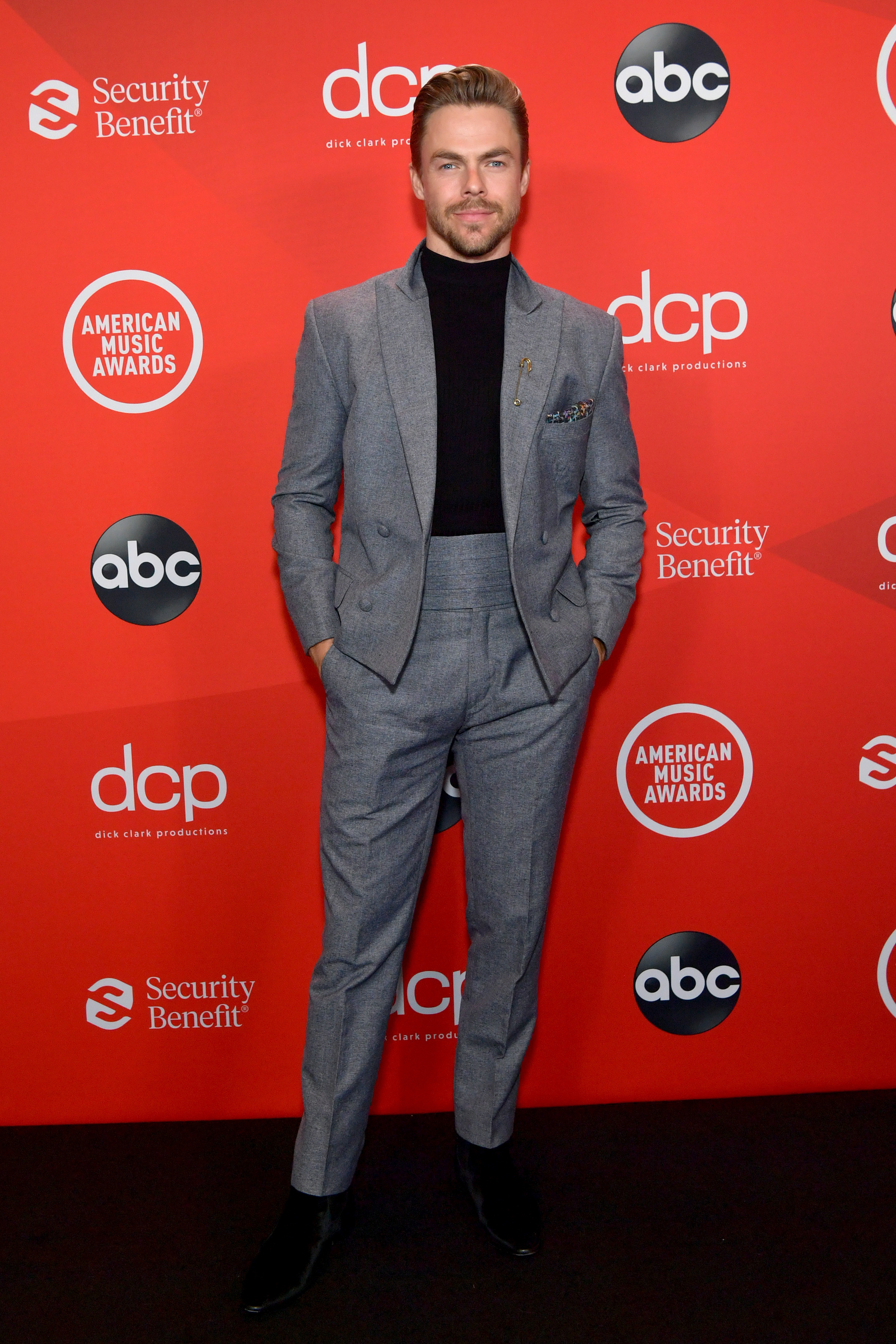 Derek Hough attends the 2020 American Music Awards wearing a jacket and high-waisted pants