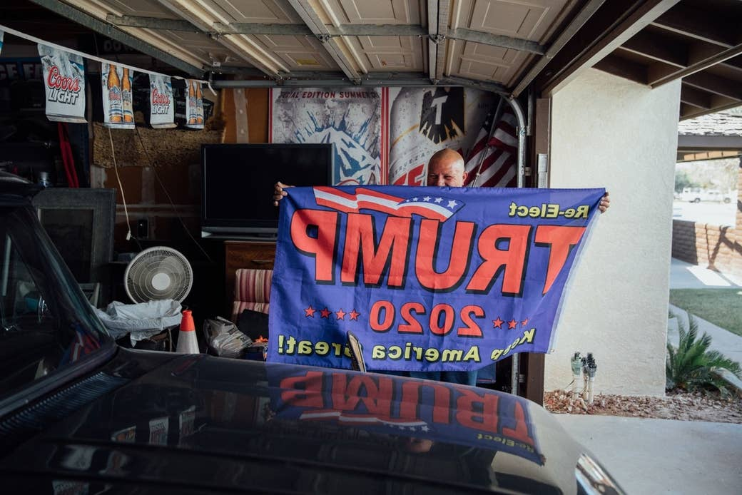 A man in his garage holds up a Trump 2020 flag behind his car
