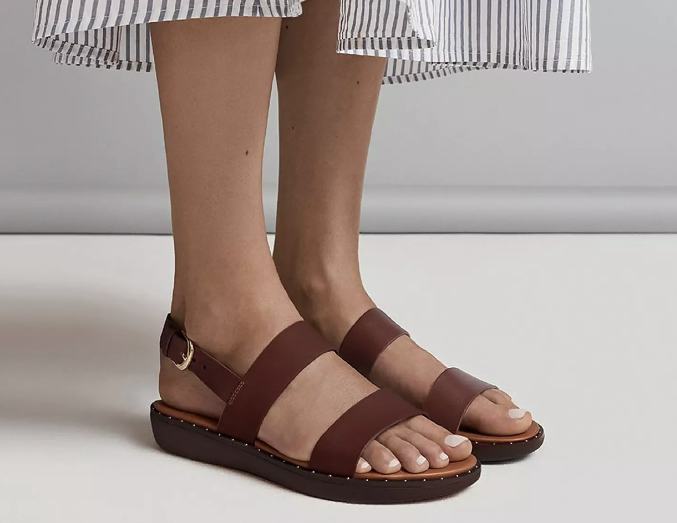 A model wearing a pair of dark brown leather sandals with small studs along the outsole