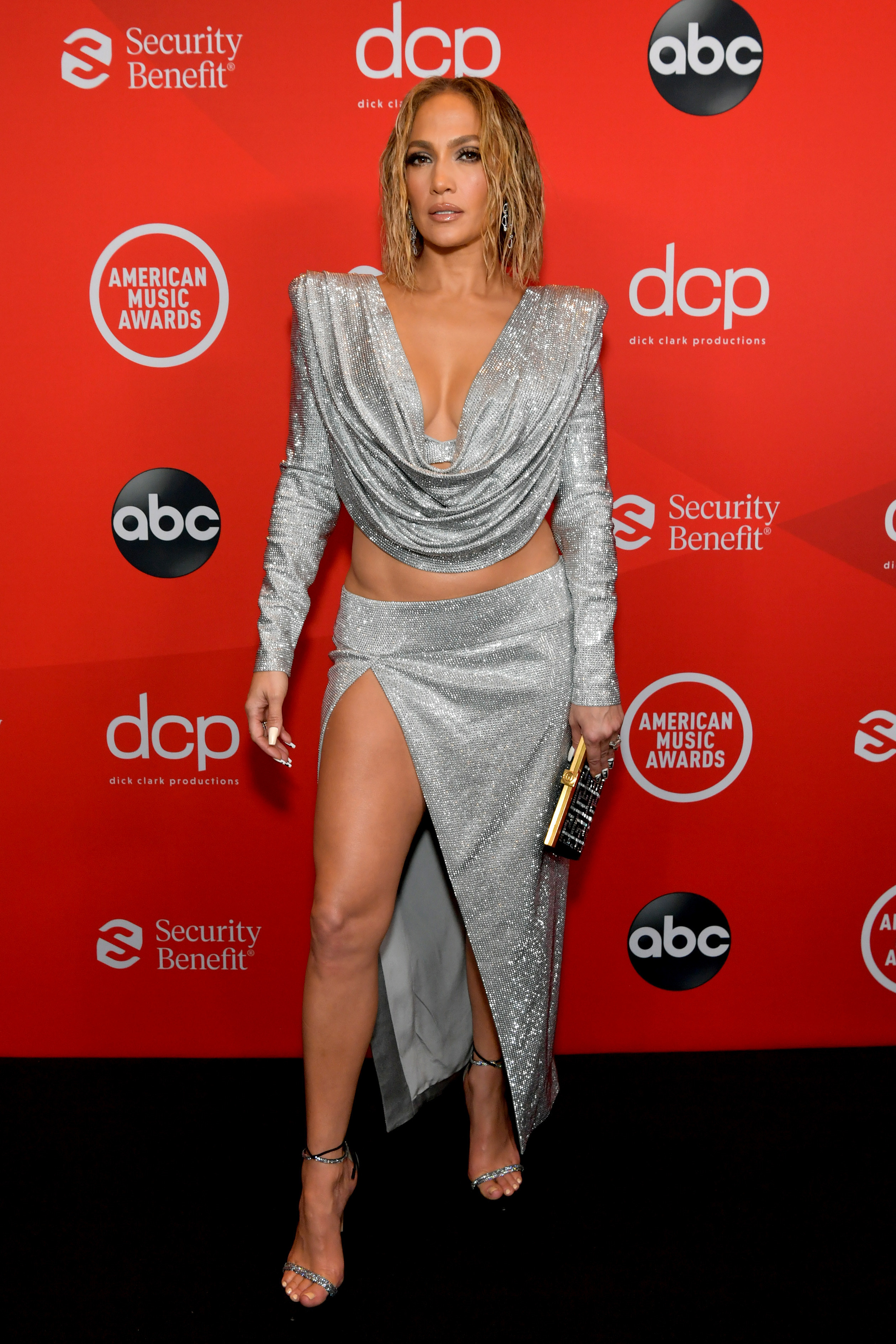 Jennifer Lopez, wearing a sparkly low-cut cowl-neck top and matching skirt, attends the 2020 American Music Awards