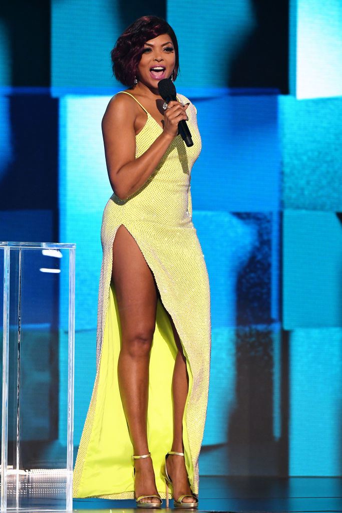 Taraji P. Henson speaks onstage for the 2020 American Music Awards in a long gown with a thigh-high slit