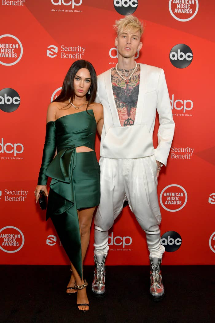 Megan Fox, wearing a one-sleeved dress, and Machine Gun Kelly, wearing a low-cut top and matching harem pants, attend the 2020 American Music Awards