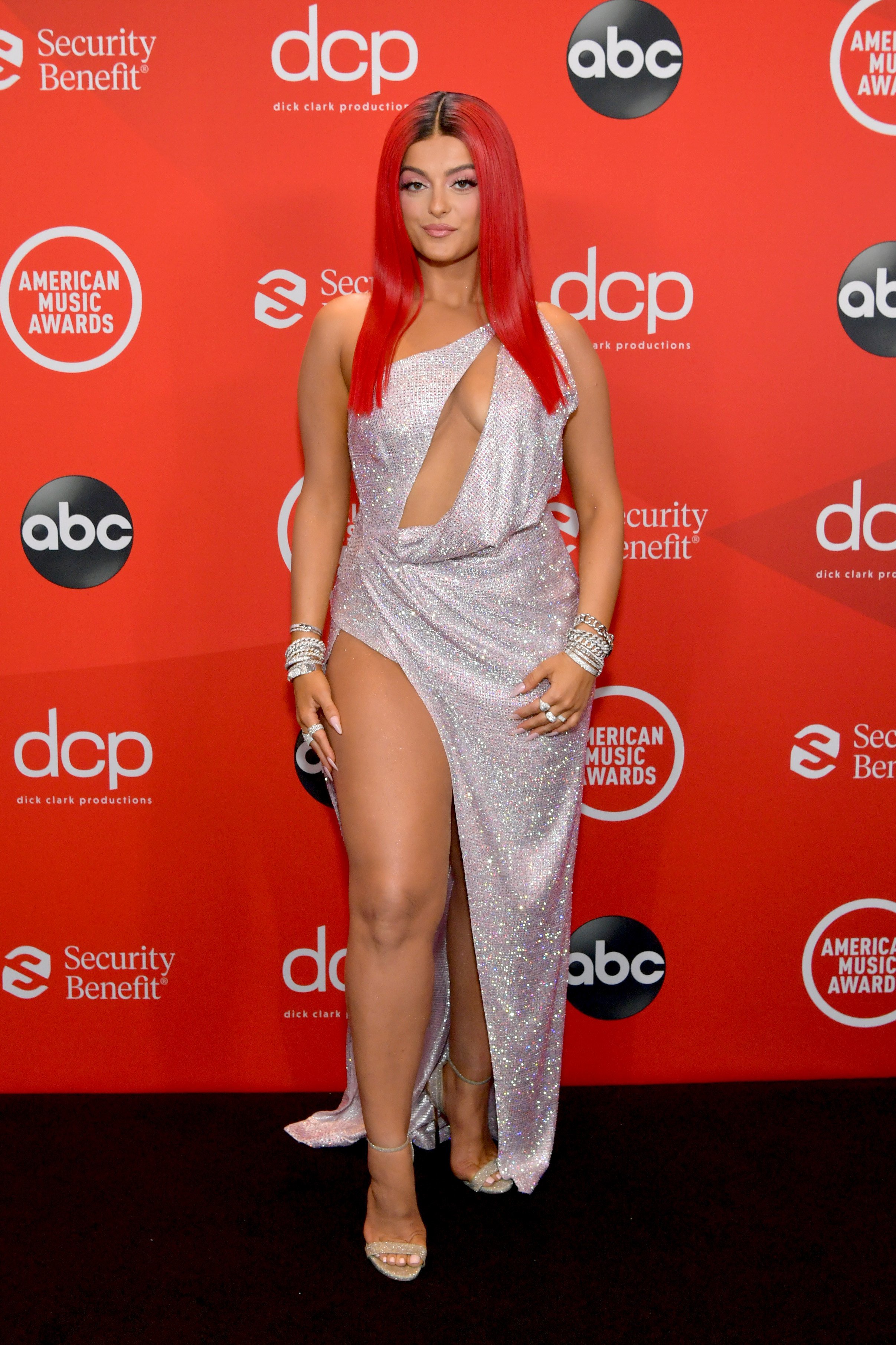 Bebe Rexha attends the 2020 American Music Awards in a sequined gown with thigh-high slit