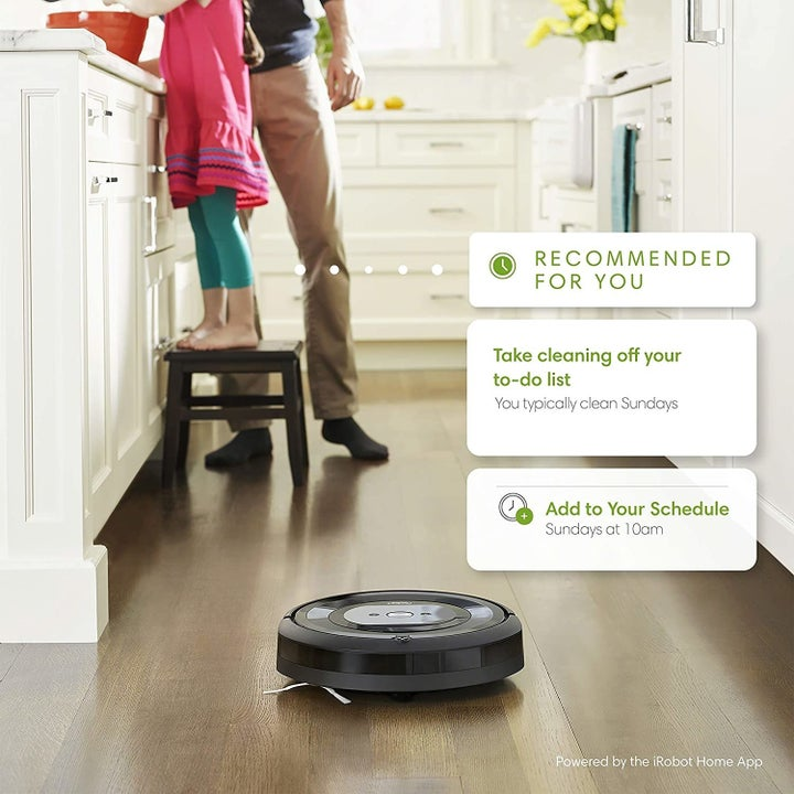 Small round black robot vacuum on a hardwood floor with text blurbs above it making cleaning recommendations