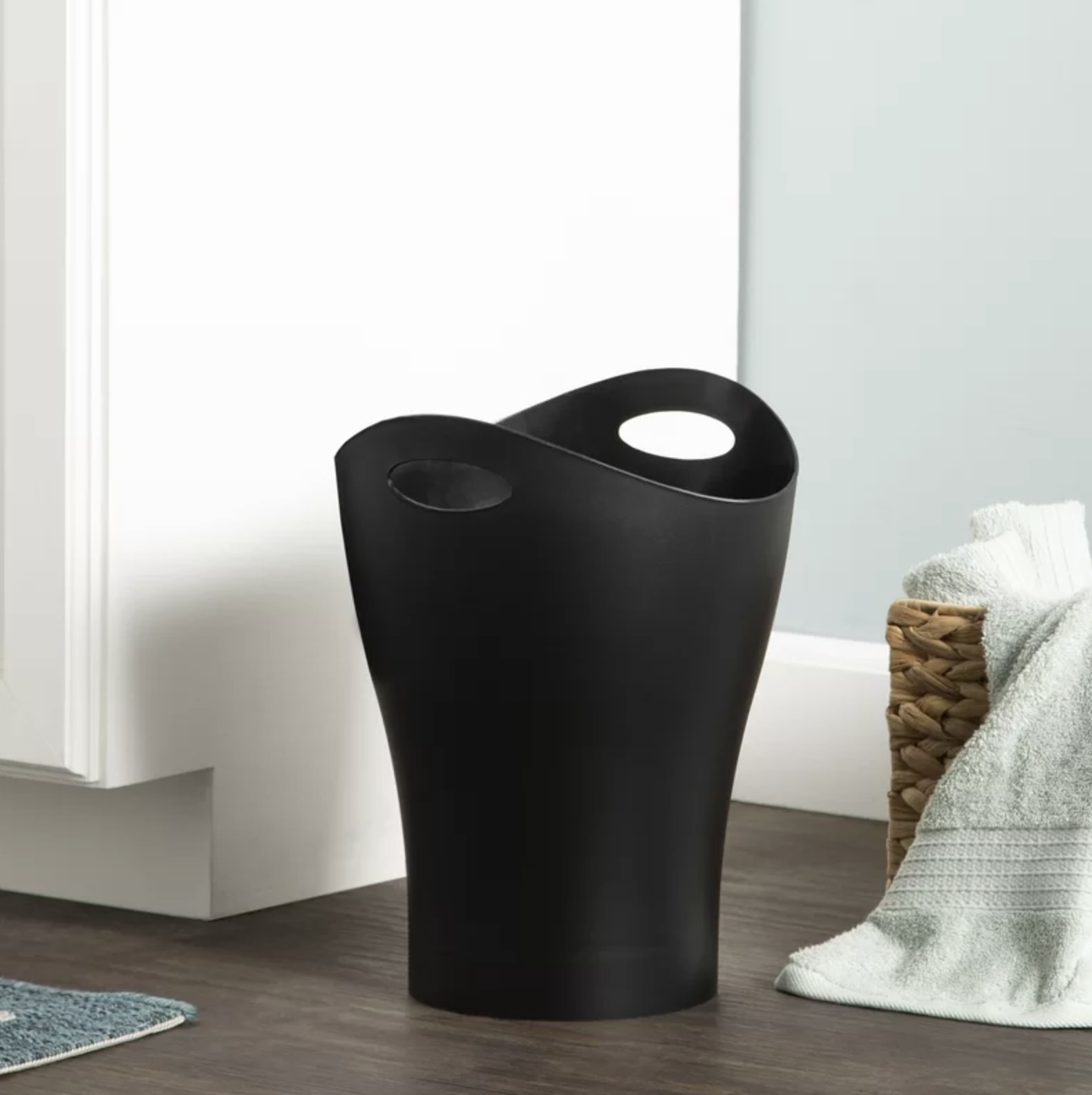 A black wastebasket
