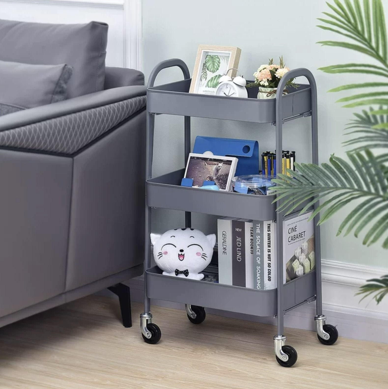 A grey three tier cart with books and decor inside