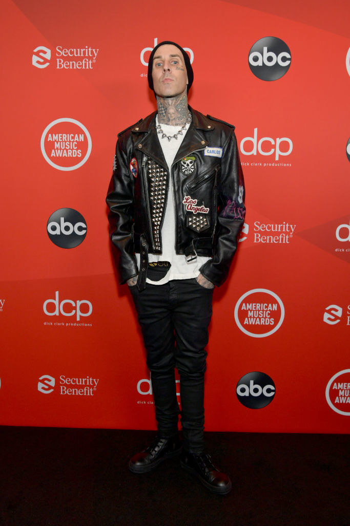 Travis Barker attends the 2020 American Music Awards in. a leather jacket, torn T-shirt, and jeans