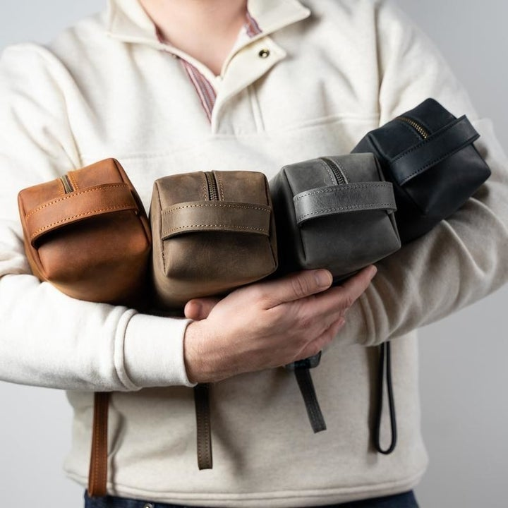 person holding leather dopp kits