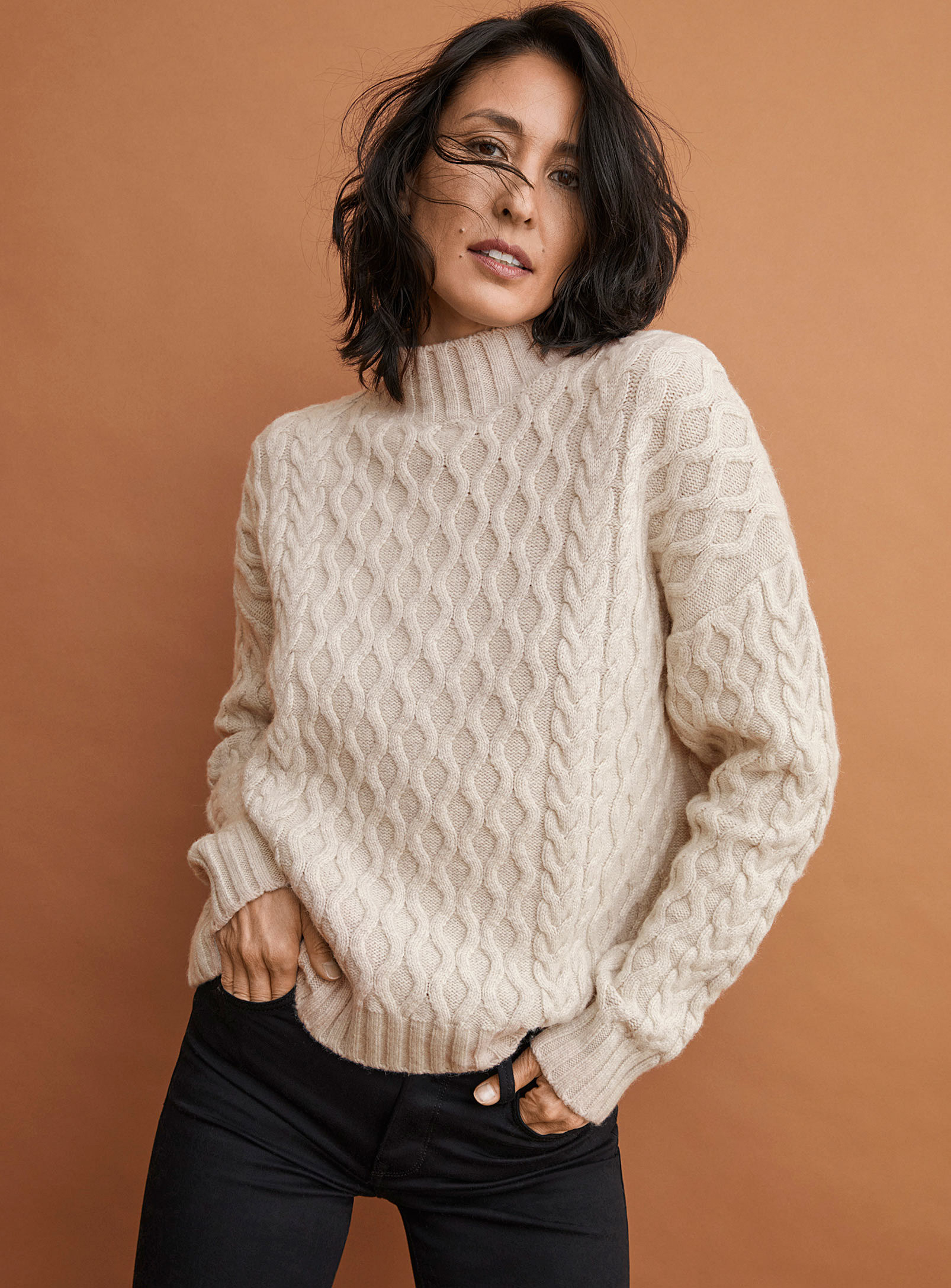 A person wearing a sweater with a wavy knit pattern