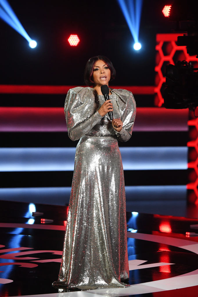 Taraji P. Henson speaks onstage for the 2020 American Music Awards in a metallic gown with voluminous shoulders