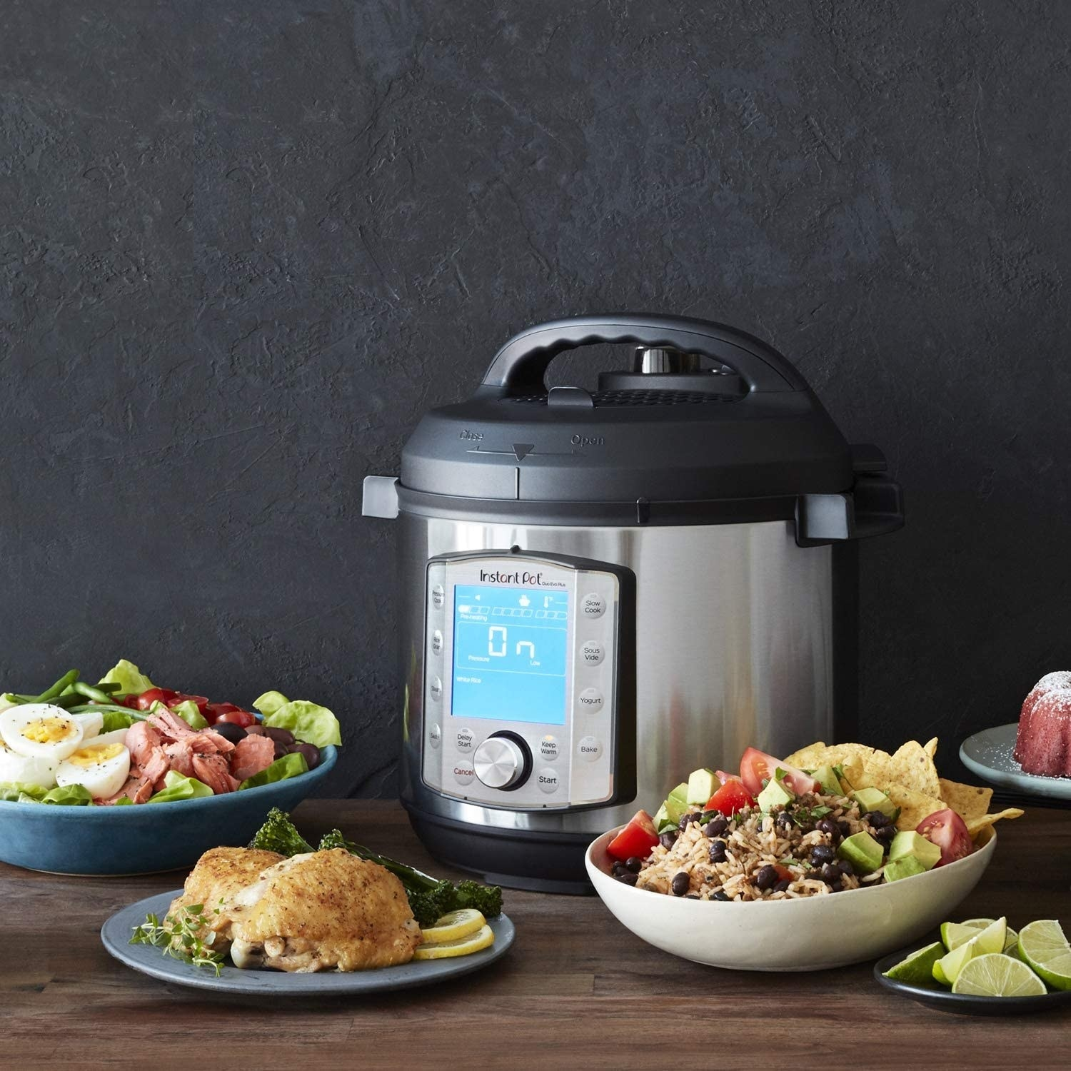 A stainless steel instant pot with a digital display surrounded by several dishes on a counter