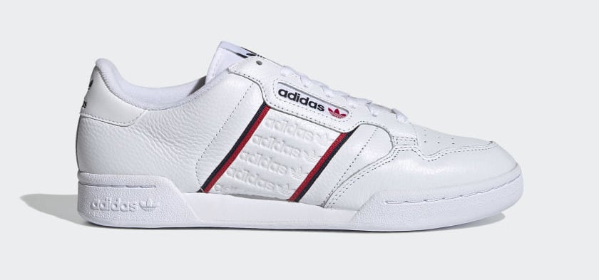 White sneakers with red and blue stripes in the middle and embossed adidas logo in the center